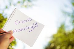 Man holding a notebook that says good morning. Man holds a notebook on a sunny day that says good morning Royalty Free Stock Photos