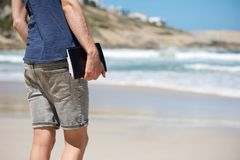 Man holding notebook while walking on the beach Royalty Free Stock Photos