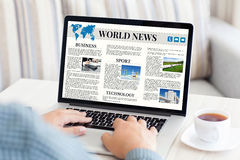 Man holding notebook with world news site on the screen Royalty Free Stock Image