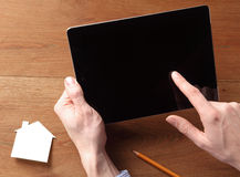 Man Holding Off Tablet While Touching the Screen Stock Images