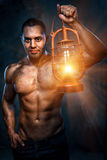 Man holding oil lamp. Muscular build man holding oil lamp Stock Photography