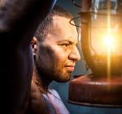 Man holding oil lamp Stock Photos