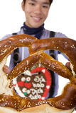 Man holding Oktoberfest Pretzel in camera Royalty Free Stock Photos