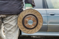 Man holding old brake disc near car Stock Photo