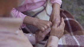 Man holding old female hands, family love and care, old couple in nursing home