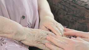Man holding old hands of elderly woman. Close up. Man holding the old wrinkled hands of elderly woman. Close up. Man soothes the elderly woman during stress stock footage