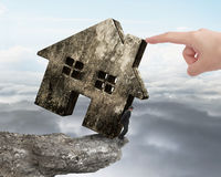 Man holding old house on cliff edge with hand pushing Stock Photography