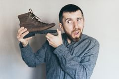 Free Man Holding Old Leather Boot With Torn Sole At His Ear, Surprise And Shock On His Face Royalty Free Stock Photography - 165592957