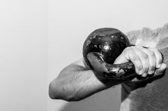 Man holding old and rusty kettle bell on his shoulder. Royalty Free Stock Photography