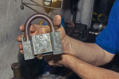 Man holding old rusty a lock in his hands. Stock Photo