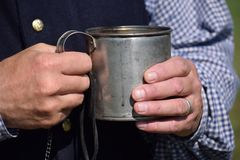 Man holding old tin cup of coffee. Man in period clothes holds an old tin of coffee with both hands at state park stock images