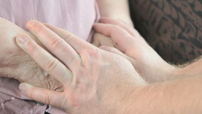 Man holding old wrinkled hands of elderly woman. Man holding the old wrinkled hands of elderly woman. Close up. Man soothes the elderly woman during stress stock footage