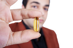 Man holding omega pill  Royalty Free Stock Image