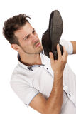 Man holding one of his shoes close to his nose Royalty Free Stock Photos