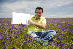 Man Holding Open Book. Young Man in a flied Holding Open Book with Blank Pages Royalty Free Stock Photo