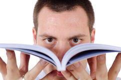 Man holding an open book in front of his face. Young man, holding a book in front of his face, looking directly into a camera Stock Photography