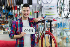 Man holding open sign in bike shop Royalty Free Stock Image