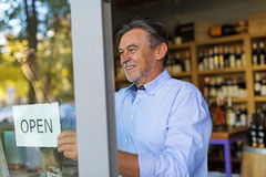 Man holding open sign in wine shop. Wine shop owner holding open sign stock photo