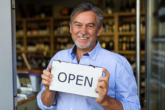 Man holding open sign in wine shop. Wine shop owner holding open sign royalty free stock photo