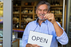 Man holding open sign in wine shop. Wine shop owner holding open sign stock images