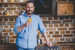 Man holding orabge juice. Smiling mid adult man holding orabge juice at the kitchen Stock Images