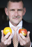 Man holding orange and apple in his hands Royalty Free Stock Images
