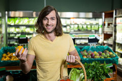 Man holding orange and basket of vegetables Royalty Free Stock Photo