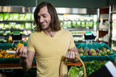 Man holding orange and basket of vegetables Stock Photos