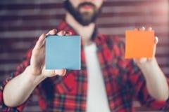 Man holding orange and blue adhesive notes Stock Photo