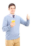 Man holding an orange juice and giving thumb up Royalty Free Stock Photo
