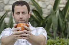 Man holding an orange mug in front of him with the mug in focus. Man holding an orange coffee mug in front of him with the mug in focus and plants in the Royalty Free Stock Photography