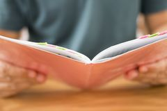 Man holding orange notebook. On wooden table Stock Images