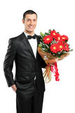 A man holding out large bouquet of gerberas Stock Photo
