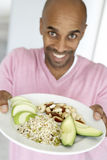 Man Holding Out A Plate With Healthy Foods. Middle Aged Man Holding Out A Plate With Healthy Foods royalty free stock photo