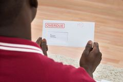 Man Holding Overdue Notice. Close-up Of African Man Holding Overdue Notice Royalty Free Stock Photos