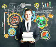 Man holding a pack of books with blackboard with busines Royalty Free Stock Photography