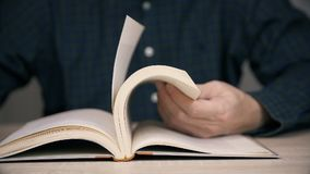 Man holding pages and browsing antique old book. Cropped view of man holding pages in hand and browsing antique book, selective focus, slow motion stock video