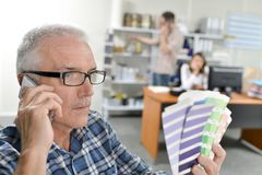 Man holding paint charts talking on telephone. Adult Stock Image