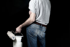 Man holding paint roller and a bucket of paint Royalty Free Stock Images