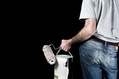 Man holding paint roller and a bucket of paint Stock Photos