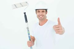 Man holding paint roller while gesturing thumbs up Stock Image