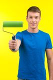 Man holding paint roller and smiling. Stock Photos