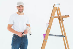 Man holding paint roller while standing by ladder Stock Images
