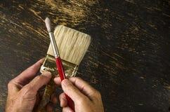 Man holding paintbrushes Stock Photography