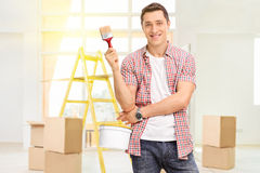 Man holding a paintbrush and a color bucket Stock Photo