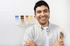 Man Holding Paintbrush In Front Of Color Samples Royalty Free Stock Images