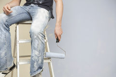 Man Holding Paintroller While Sitting On Stepladder. Midsection of man holding paintroller while sitting on stepladder against wall Stock Photo