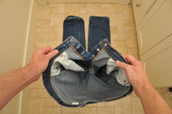 Man holding pants before putting them on. Above view of man putting pants on Stock Image