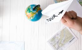 A man is holding a paper airplane in his hand. Still life of a traveler. Stock Photography
