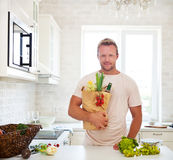 Man holding paper bag full of groceries on the kitchen Royalty Free Stock Image